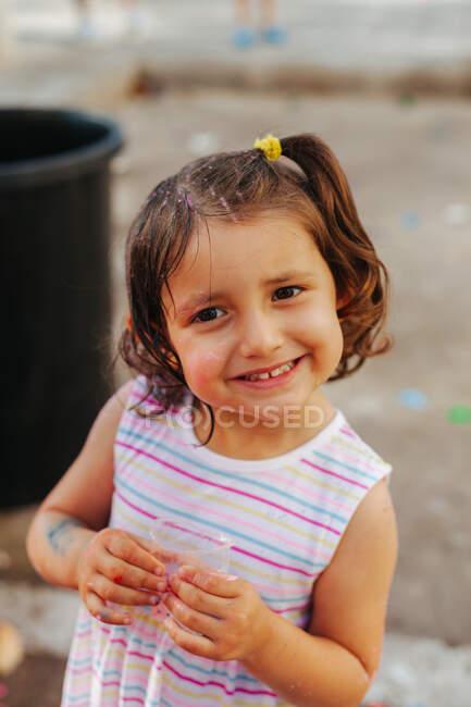 Alto ángulo de niña feliz sonriendo y apretando la taza mientras se divierten durante el festival de pintura - foto de stock