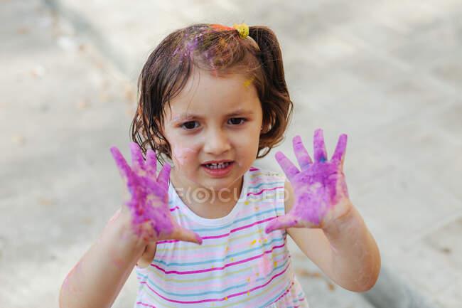 Зверху мила дівчинка демонструє фіолетові руки, розважаючись під час свята фарби. — стокове фото
