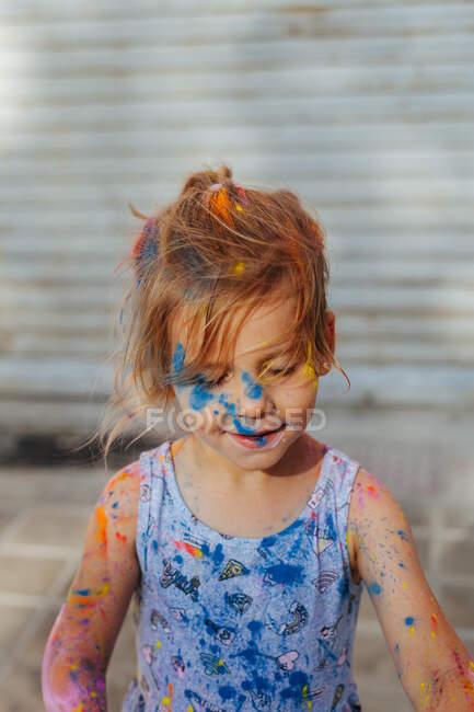 Carino bambina coperta viso e corpo in vernice sporca durante il festival di vernice sulla strada della città — Foto stock