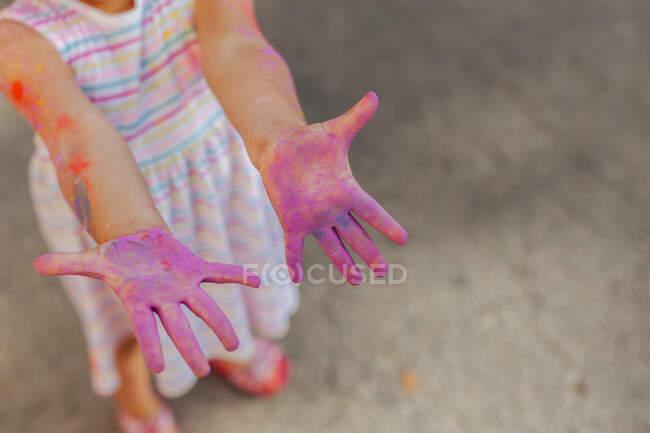Dall'alto ritagliato irriconoscibile carina bambina dimostrando mani viola divertendosi durante il festival di vernice — Foto stock