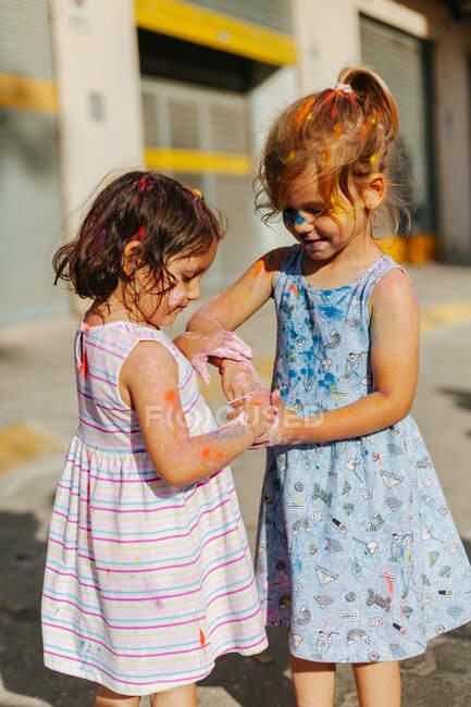 Petits amis en robes jouant avec la tasse avec des pigments lumineux pendant le festival le jour d'été dans le parc — Photo de stock