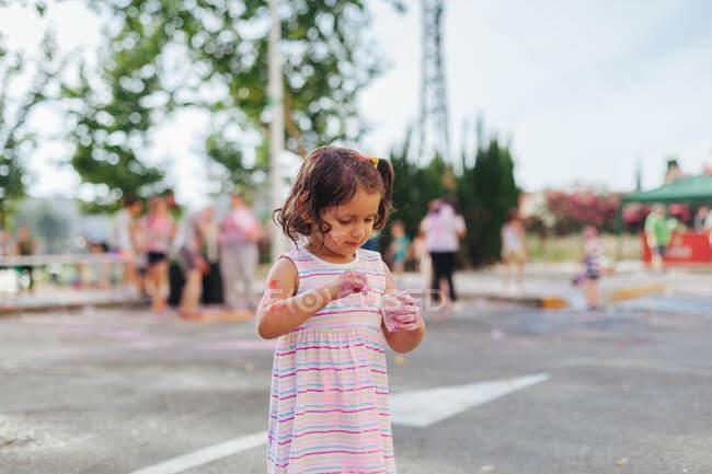 Petite fille concentrée serrant une tasse en plastique avec du pigment pendant le festival de peinture le jour d'été dans le parc — Photo de stock