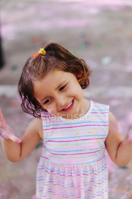 Cute little girl covered face and body in dirty paint during paint festival on city street — Stock Photo