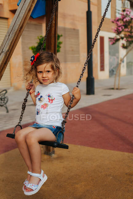 Full length little girl sitting on swing and looking at camera while resting on playground on sunny summer day — Stock Photo