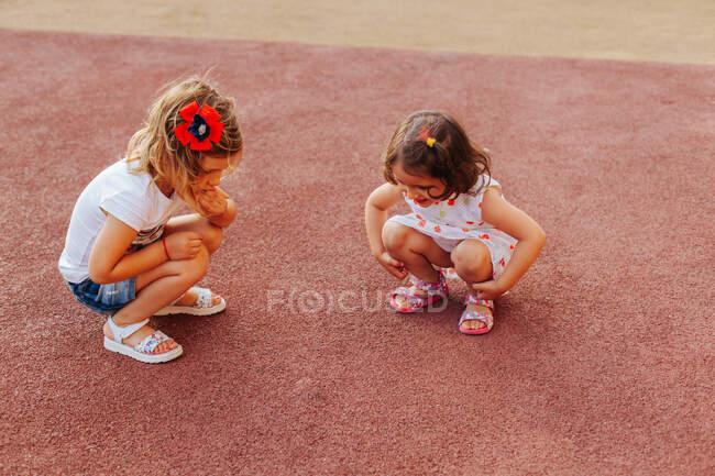 Amiguinhos de comprimento total sentados em assombrações e examinando o chão de borracha vermelha enquanto passam tempo no playground juntos — Fotografia de Stock