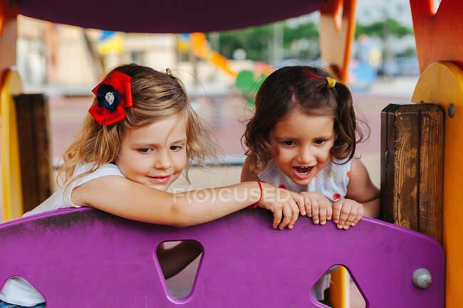 Приємні маленькі друзі, які витріщаються, розважаючись на ігровому майданчику. — стокове фото