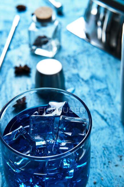 Синий напиток и инструменты бармена на столе — стоковое фото