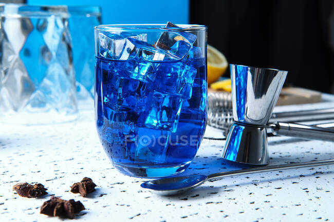 Tasty fresh blue cocktail with ice cubes and barmen tools on table — Stock Photo