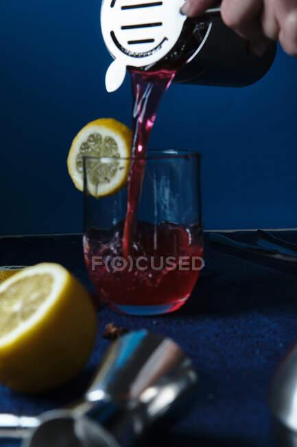 Неузнаваемый бармен наливает красный коктейль в стекло во время работы на синем прилавке — стоковое фото