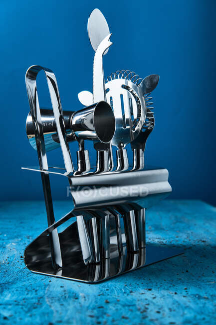 Professional contemporary shiny stainless steel barman equipment in stand on blue counter — Stock Photo