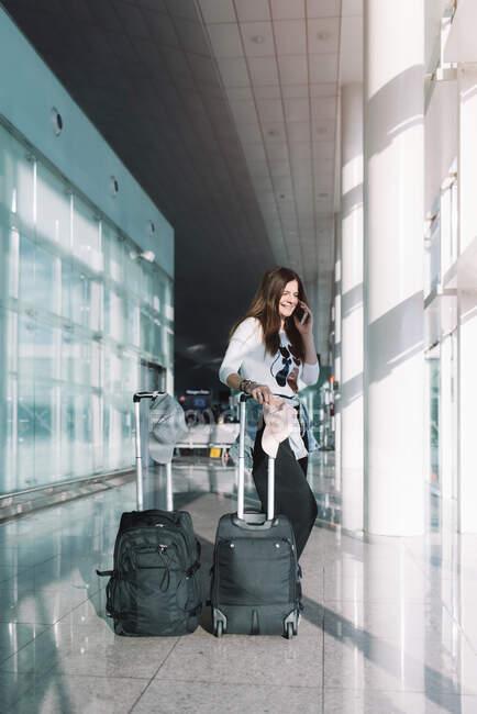 Femme calme utilisant le téléphone à l'aéroport — Photo de stock