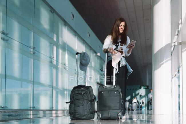 Снизу молодая женщина в повседневной одежде с багажом серфинг смартфон ждет отъезда в аэропорту — стоковое фото