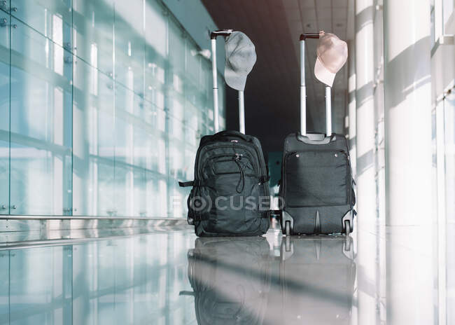 Bags with caps in airport luggage on floor waiting for departure on sunny day — Stock Photo