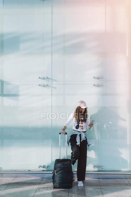 Mulher calma usando telefone no aeroporto — Fotografia de Stock