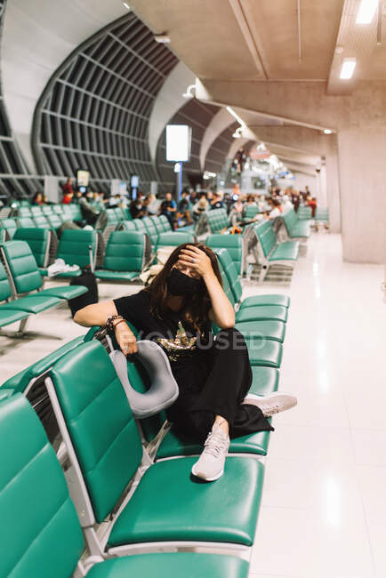 Frustrated female tourist with mask touching head in airport — Stock Photo