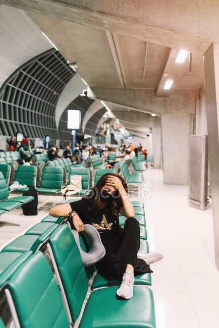 D'en haut de la jeune femme inquiète avec les jambes croisées portant le masque touchant la tête assis sur la chaise à l'aéroport — Photo de stock