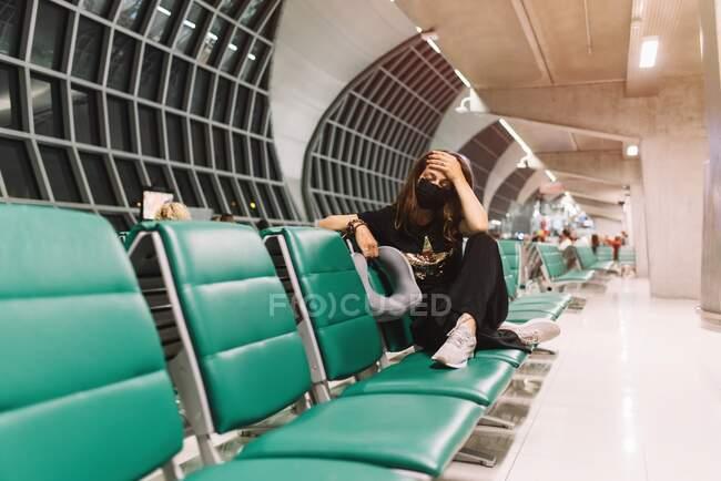 Разочарованная туристка с маской, касающейся головы в аэропорту — стоковое фото