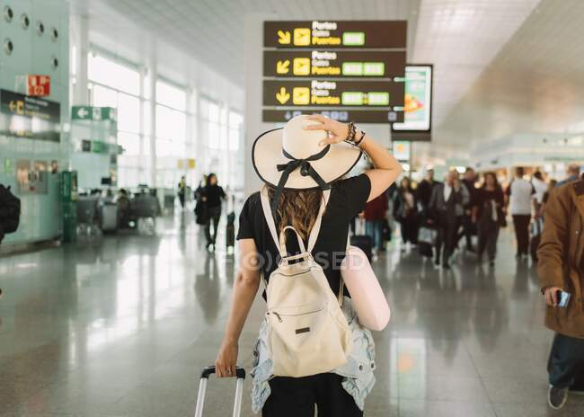 Back view of female in hat touching head carrying baggage looking at timetable in airport — Stock Photo