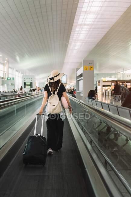 Vista posteriore della donna in abbigliamento casual e cappello con bagagli che camminano sulla scala mobile in aeroporto — Foto stock