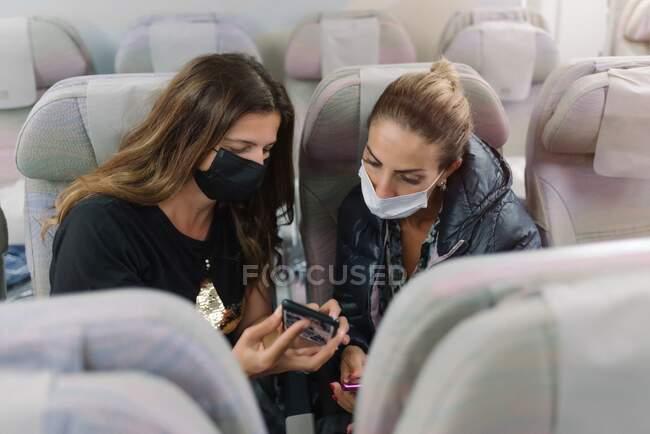 Mulher com máscara mostrando smartphone para amigo no avião — Fotografia de Stock