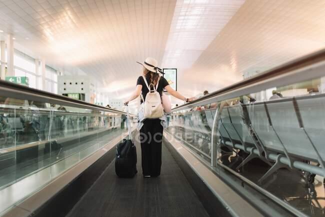 Пассажир с багажом на эскалаторе — стоковое фото