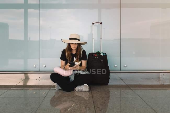 Giovane donna in cappello e abbigliamento casual seduta in posa di loto sul pavimento messaggistica su smartphone in attesa di volo in aeroporto — Foto stock