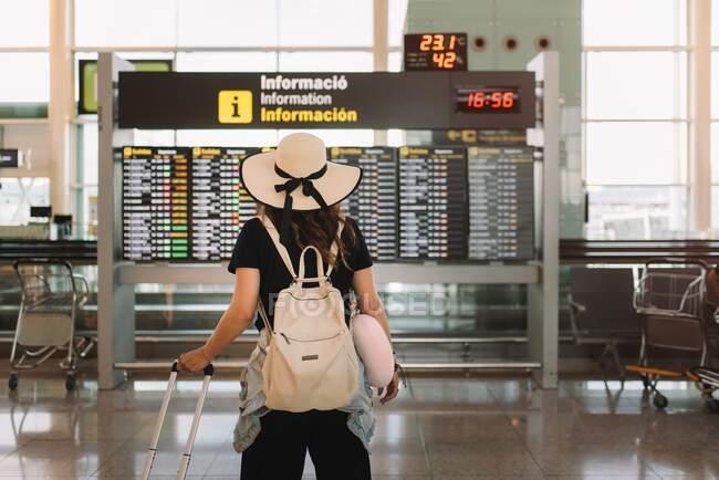 Vue arrière de la femme en chapeau avec valise et oreiller regardant l'horaire à l'aéroport — Photo de stock