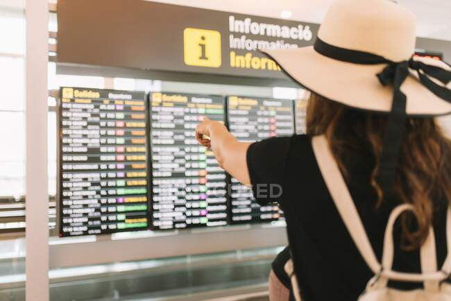 Tourist with suitcase looking at schedule in airport — Stock Photo