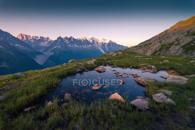 D'en haut petit lac limpide avec pierre sur le fond reflétant ciel haut dans les montagnes à Chamonix, Mont-Blanc — Photo de stock