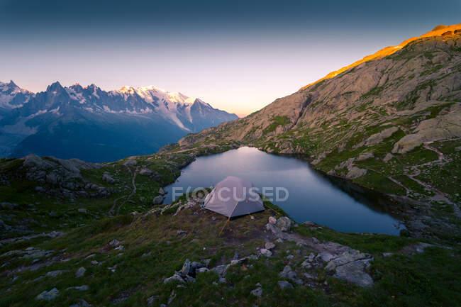 Lac et tente en cristal dans les montagnes enneigées au soleil — Photo de stock