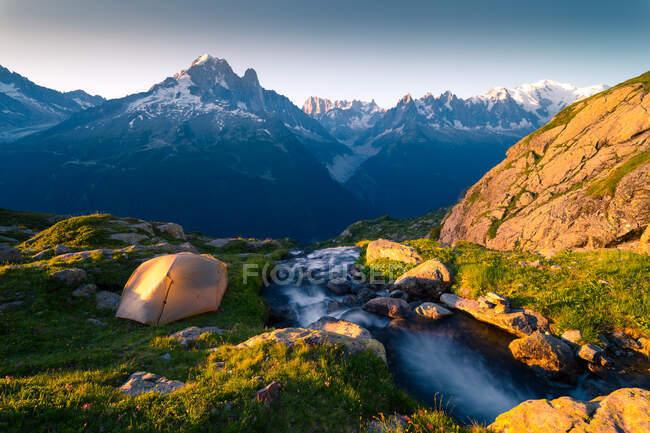 Rivière et tente en cristal dans les montagnes enneigées au soleil — Photo de stock