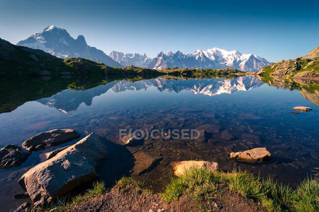 Lac cristallin reflétant les montagnes enneigées par beau temps — Photo de stock