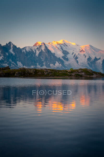 Bezaubernde Landschaft mit hügeligem Ufer und See, die den Sonnenuntergang im Himmel und die schneebedeckten Berge in Chamonix, Mont-Blanc widerspiegelt — Stockfoto