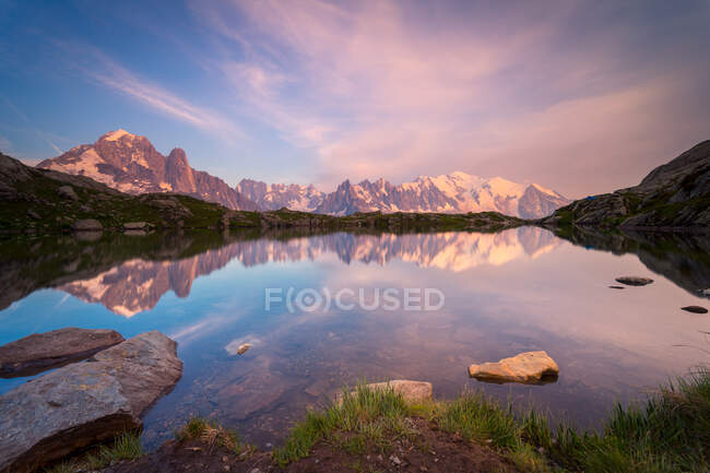 Crystal lake reflecting snowy mountains in bright day — Stock Photo