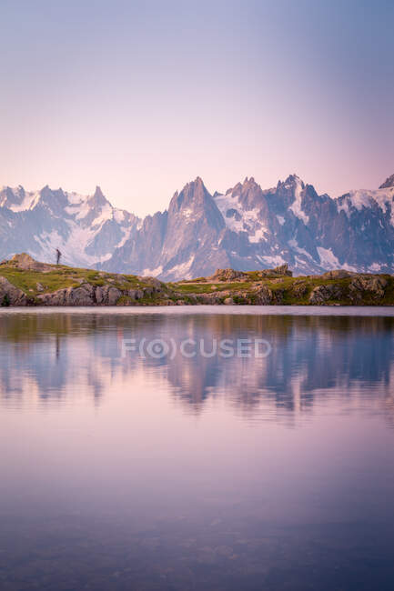 Lonely tourist on hilly shore reflecting in crystal lake in snowy mountains under sunlight. - foto de stock