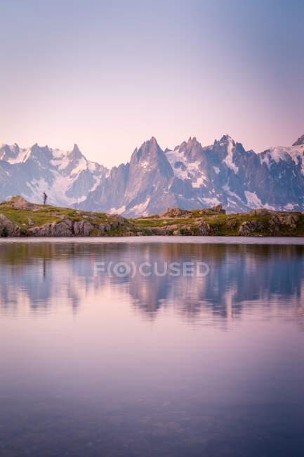 Einsamer Tourist am hügeligen Ufer, der sich im kristallklaren See in den schneebedeckten Bergen im Sonnenlicht spiegelt — Stockfoto