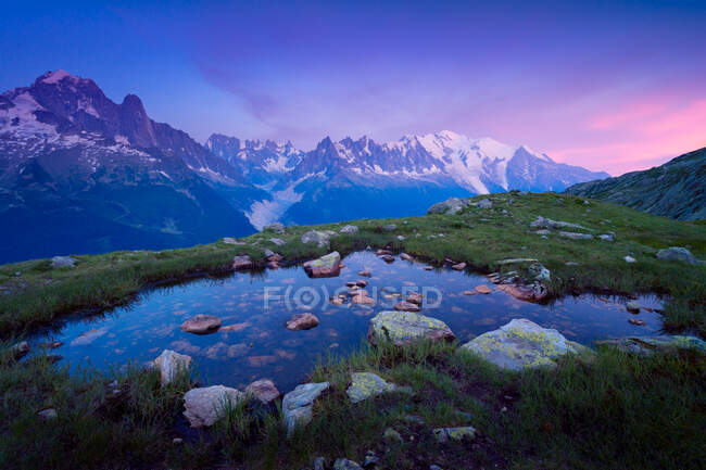 Pequeño lago pedregoso en la colina de hierba en las montañas nevadas - foto de stock