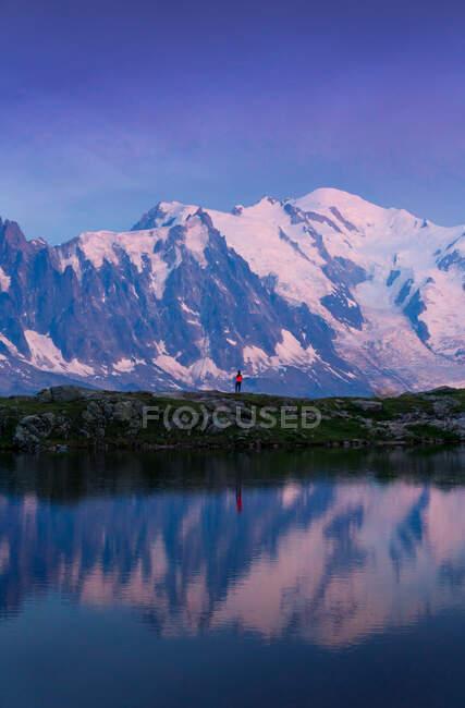 Touriste calme en vêtements rouges profitant d'une vue sur la montagne reflétant dans un lac clair par temps ensoleillé à Chamonix, Mont-Blanc — Photo de stock