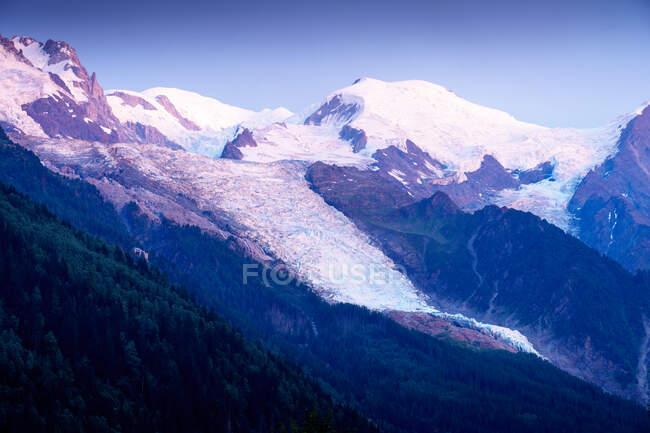 Montagnes blanches et pointues dans la neige s'élevant jusqu'au ciel nuageux — Photo de stock