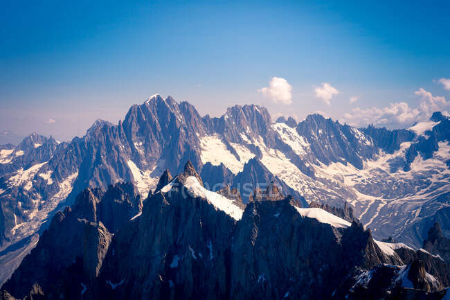 White sharp mountain peaks in snow raising up to cloudy sky — Stock Photo