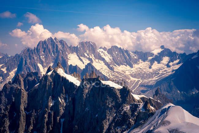 Weiße, scharfe Berggipfel im Schnee, die in den wolkenverhangenen Himmel ragen — Stockfoto