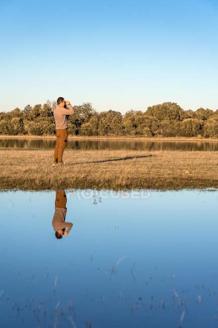 Vista laterale di un uomo irriconoscibile che guarda attraverso un vecchio binocolo la fauna di una laguna in Spagna — Foto stock