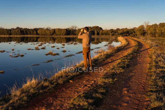 Seitenansicht eines unkenntlichen Mannes, der durch ein altes Fernglas die Fauna einer Lagune in Spanien betrachtet — Stockfoto