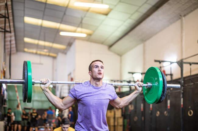 М'язовий хлопець піднімає дзвоник в сучасному спортзалі — стокове фото