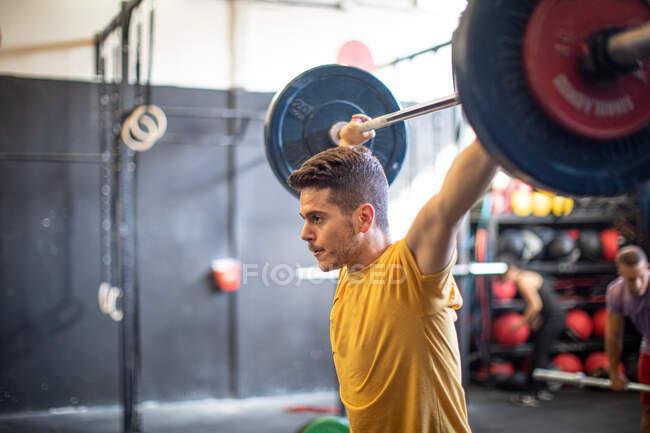 Мускулистый парень поднимает штангу в современном спортзале — стоковое фото