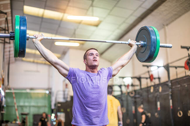 Muscular guy lifting barbell in modern gym — Stock Photo