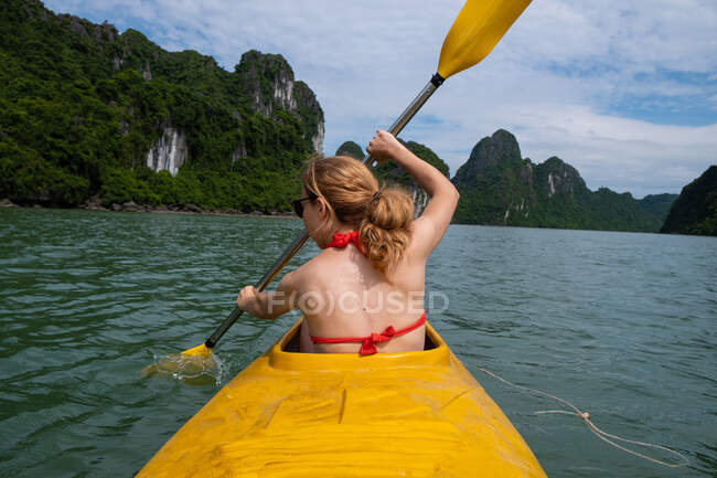 Back view of unrecognizable woman in swimsuit paddling in yellow canoe during vacation in Vietnam — Stock Photo