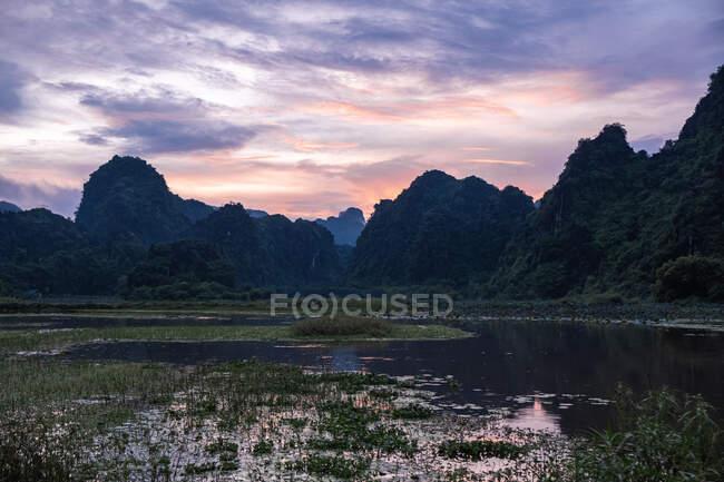 Meraviglioso scenario di tramonto colorato e montagne verdi in terreno paludoso in Giappone — Foto stock