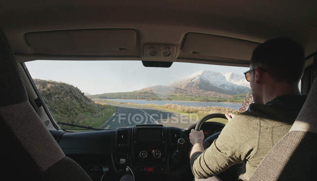 Vista posteriore del guidatore maschio senza volto che guarda la strada mentre guida un veicolo su un terreno di montagna in Irlanda — Foto stock