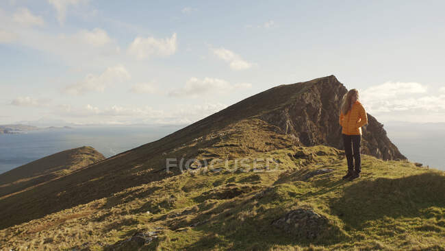 Carefree woman enjoying wonderful nature landscape and sea while standing on cliff in Ireland looking away — Stock Photo